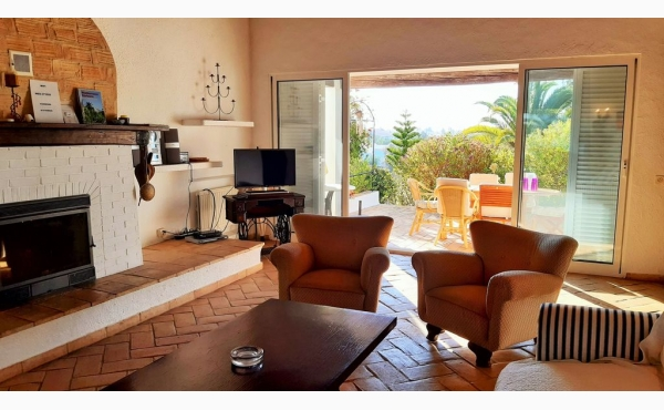 Wohnzimmer mit Kamin und Zugang zur Terrasse / Livingroom with fireplace and entrance to the terrace